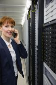 Smiling technician talking on phone while looking at server in large data center