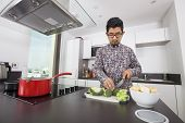 Man cutting broccoli at kitchen counter
