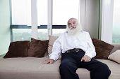 Portrait of senior man relaxing on sofa in apartment
