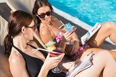 Two beautiful young women with drinks by swimming pool