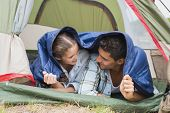 Happy young couple lying in tent on countryside landscape
