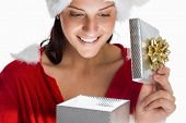 Smiling woman opening christmas present on white background