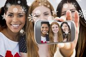 Hand holding smartphone showing close up portrait of cheerful female friends