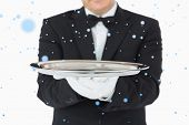 Man holding a silver tray with both hands against snow falling
