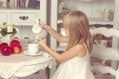 Girl Sitting At The Table With Fruits And Teapot