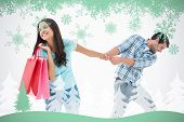 Attractive young man pulling his shopaholic girlfriend against snowflakes and fir tree in green