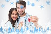 Happy young couple holding new house key against snowflakes and fir trees