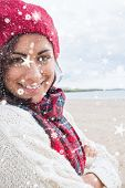 Woman in knitted hat and pullover smiling at beach against snow falling