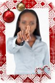 Portrait of a businesswoman touching an invisible screen against christmas themed page