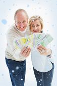 Happy mature couple smiling at camera showing money against snow falling