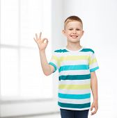 childhood, home, gesture and people concept - smiling little boy in casual clothes making ok gesture over white room background