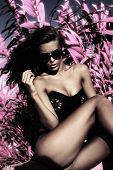 fashion model with sunglasses  in black top and bikini infrared leaves in background