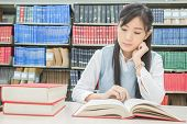 Asian Student With Open Book Reading It In College Library