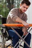 Man On Wheelchair Preparing Iron Board