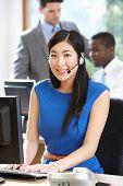 Businesswoman Wearing Headset Working In Busy Office