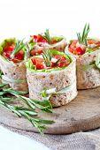 Salmon lavash rolls with fresh salad leafs