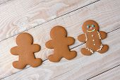 HIgh angle view of three gingerbread men on a rustic white kitchen table. Two cookies are  plain and without icing while one is decorated with icing and candies..