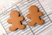 HIgh angle view of two gingerbread men on a cooling rack. The wire rack is on a rustic white kitchen table. The cookies are  plain and without icing.