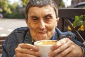 Closeup portrait of elderly disabled man with cerebral palsy, at an outdoor cafe.