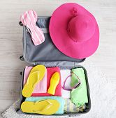 Suitcase with things on white carpet on the floor for travelling somewhere close to water for spending summer vacation