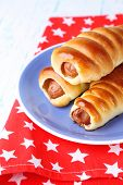 Baked sausage rolls on plate on table close-up