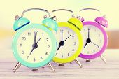 Colorful alarm clocks on table close-up