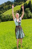 Attractive blonde woman in a dirndl is full of joy