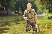 Mature fisherman holding a fish and fishing rod in a river