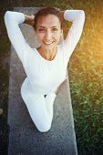 Portrait of a young woman smiling makes yoga outdoors