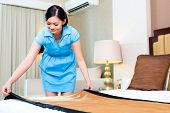 Chambermaid making bed in Asian hotel room
