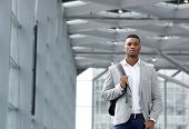 Cool Young Man Walking Inside Station Building With Bag