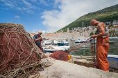 DUBROVNIK, CROATIA - MAY 26, 2014: Local fishermen in city port holding fishing net. Thanks to local fishermen Dubrovnik is brimming with fresh seafood.