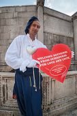 DUBROVNIK, CROATIA - MAY 27, 2014: Man wearing old traditional clothes holding big souvenir heart in front of Onofrio's fountain. Dubrovnik has many shops selling authentic local craft and souvenirs.
