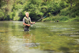 stock photo of rod  - Mature fisherman fishing in a river with a fishing rod - JPG