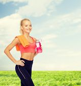 sport, exercise and healthcare - sporty woman with orange towel and water bottle