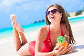 young woman in swimsuit and straw hat in sunglasses with coconut on beach