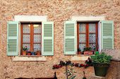 stock photo of stone house  - Two french rustic windows with old green shutters and flower pots in stone rural house - JPG