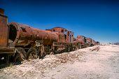 stock photo of graveyard  - Old locomotive graveyard in desert near Salar de Uyuni in Bolivia - JPG