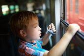 Little boy with toy looking out of train window