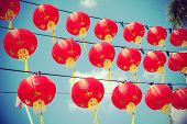 Retro Filtered Chinese Red Paper Lanterns Against Blue Sky