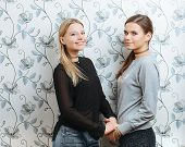 Lifestyle portrait of two young best friends hipster women holding hands and posing indoors