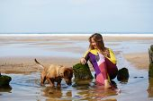 Постер, плакат: Professional surfer girl taking a break sitting against the ocean young surfer girl in wets suit