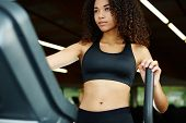 image of time machine  - Beautiful afro american woman with curly hair exercising in gym on a step simulator machine beautiful and healthy woman enjoying time at gym - JPG