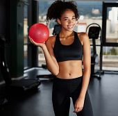 Portrait of pretty afro american girl holding pilates toning ball at gym