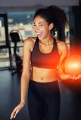 Portrait of african american woman with stunning smile holding fit ball at gym