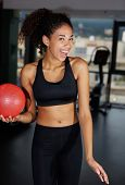Portrait of young happy girl gives a cute smile to you while working out at gym