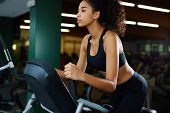 image of health center  - Attractive sexy woman with perfect figure riding on spin bike at fitness center