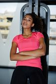 Portrait of dark skinned athletic girl relaxing after workout and looking to the camera