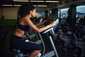 Side view picture of young woman with curly afro hair exercising on cardio spinning bike at gym
