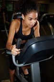 Portrait of focused afro american girl working out on spinning bike at gym